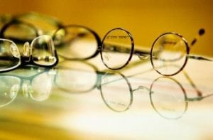 several pairs of glasses on a glass top surface