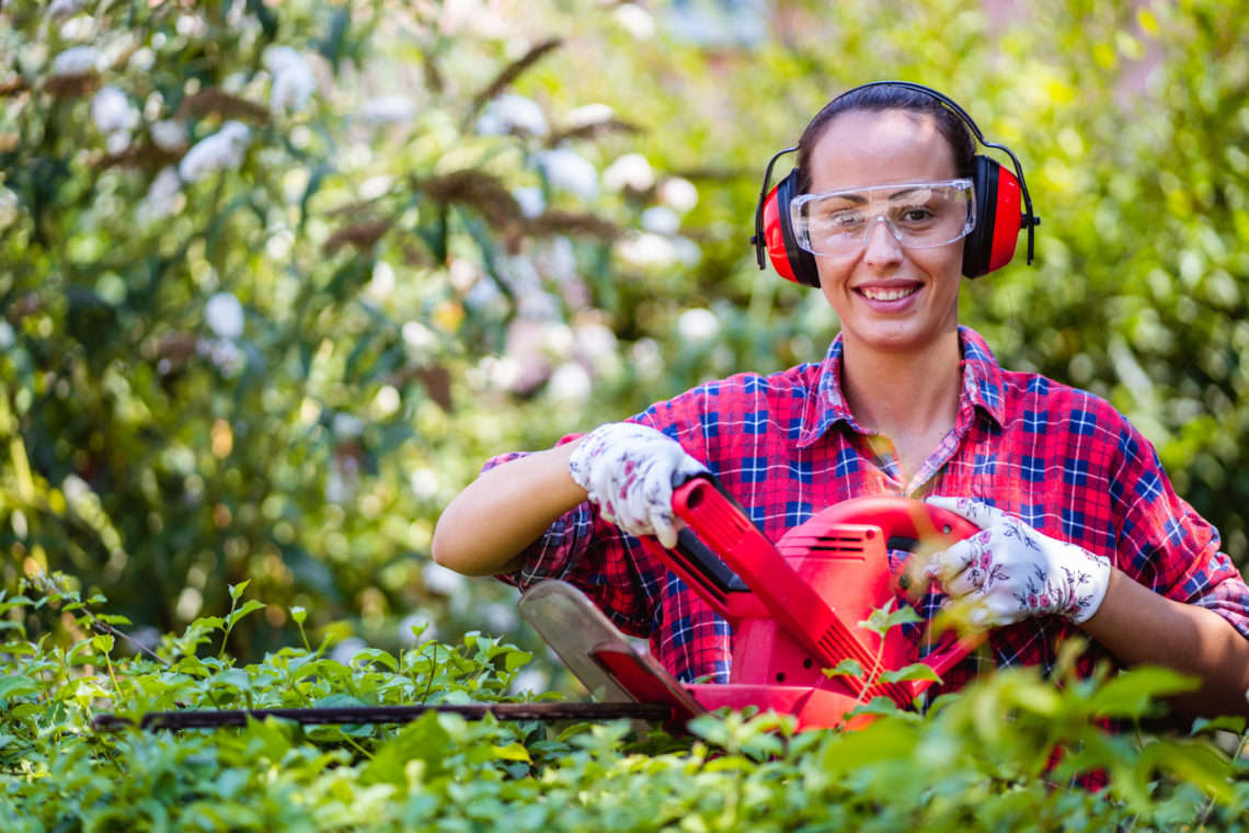 woman using hedge trimmers with safety glasses