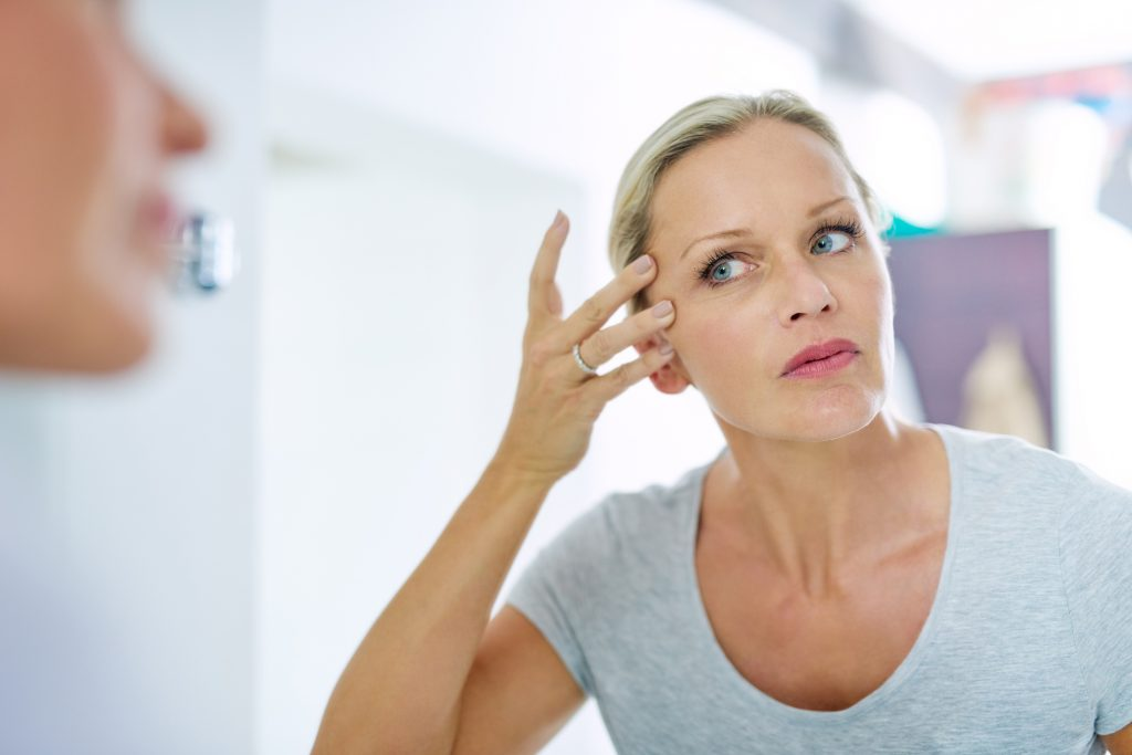 Cropped shot of a mature woman inspecting her skin in front of the bathroom mirror